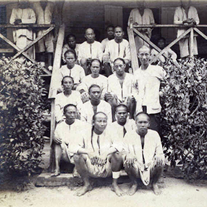 A group of early Christmas Island Coolies sitting on steps
